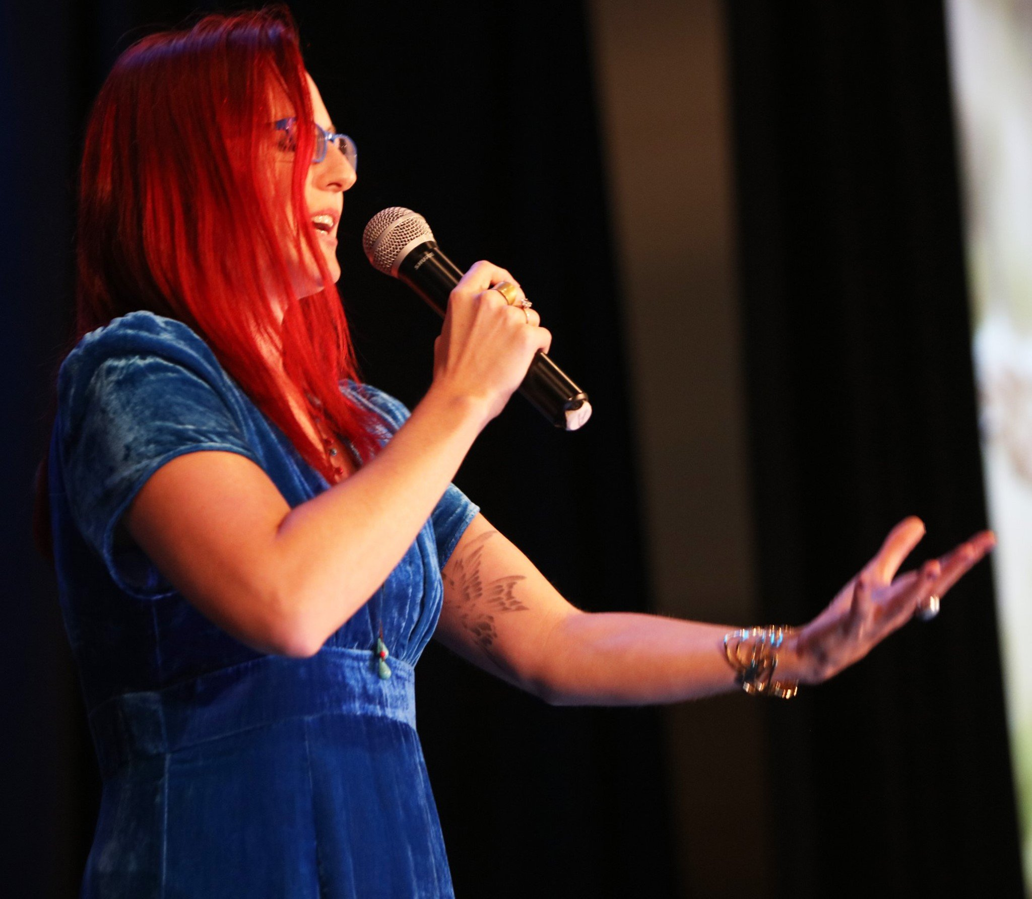 Stasha on stage speaking into microphone in one hand, other open wide to audience
